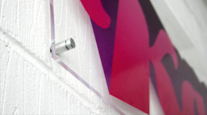 Example of a clear acrylic sign with wall mounts